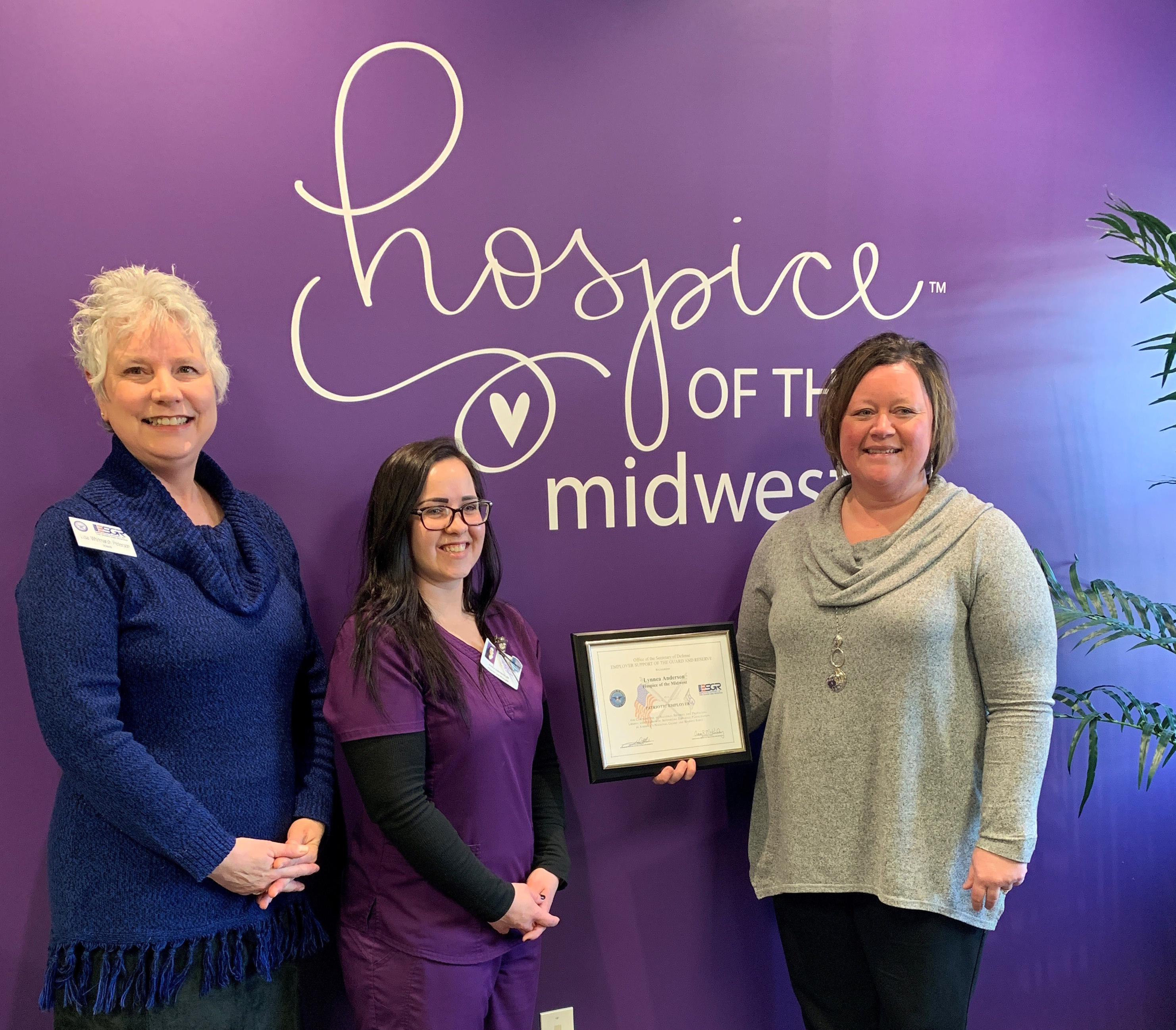 The ESRG office awarding Lynnea Andersen The Patriot Award for valiant efforts in supporting and honoring those who have or are serving our country and working for Hospice of the Midwest