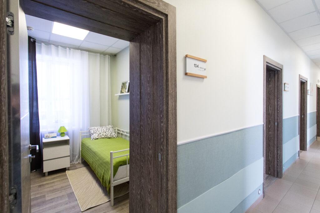 nursing home hallway, room with green bedding, wood frame door