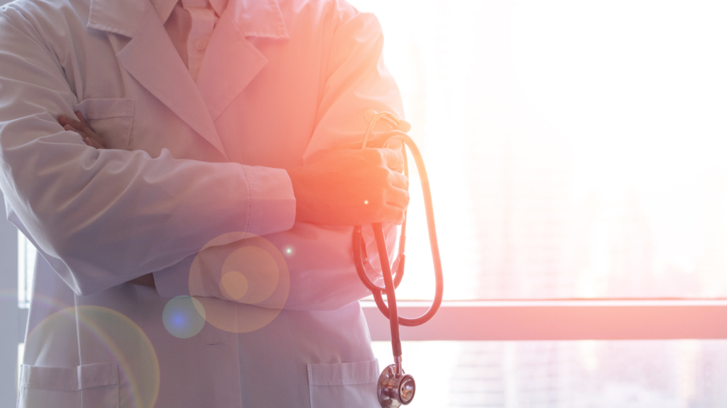Close up of doctor's crossed arms holding a stethoscope and wearing a white lab coat