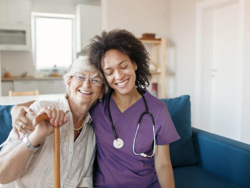 Portrait of Smiling Senior Woman and Her Mixed Race Female Caregiver Together at Nursing Home. Caring Female Doctor Taking Care of a Happy, Elderly Woman